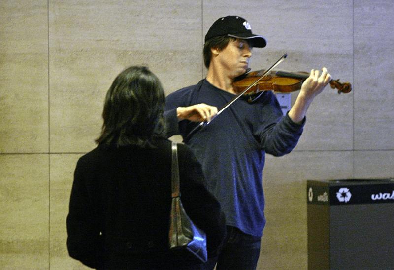 Fotografía de un músico ambulante tocando el violín en el transporte público