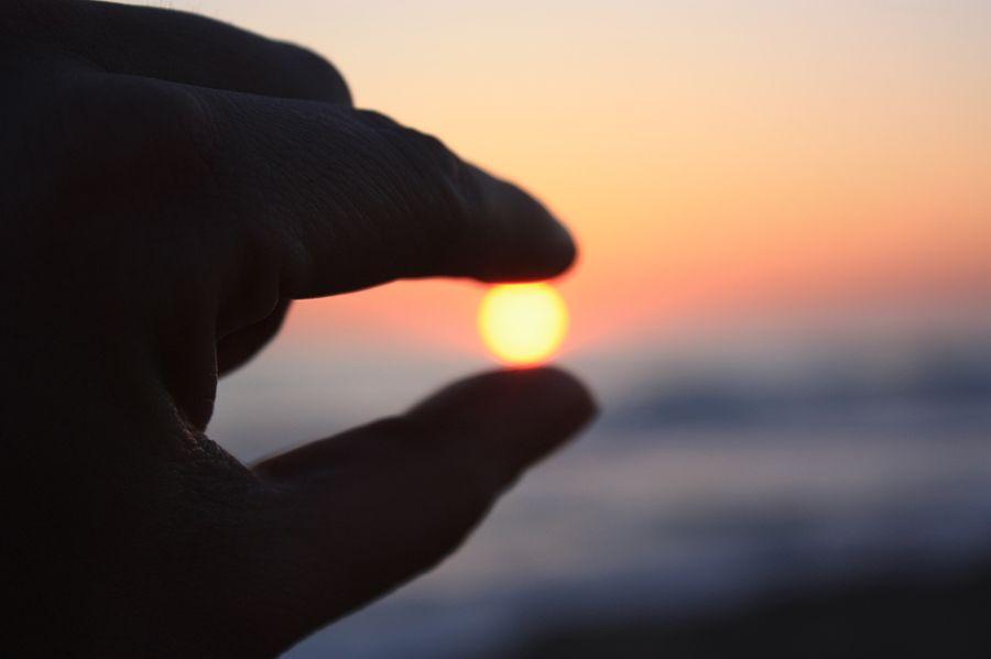 Fotografía de una mano que parece atrapara al sol