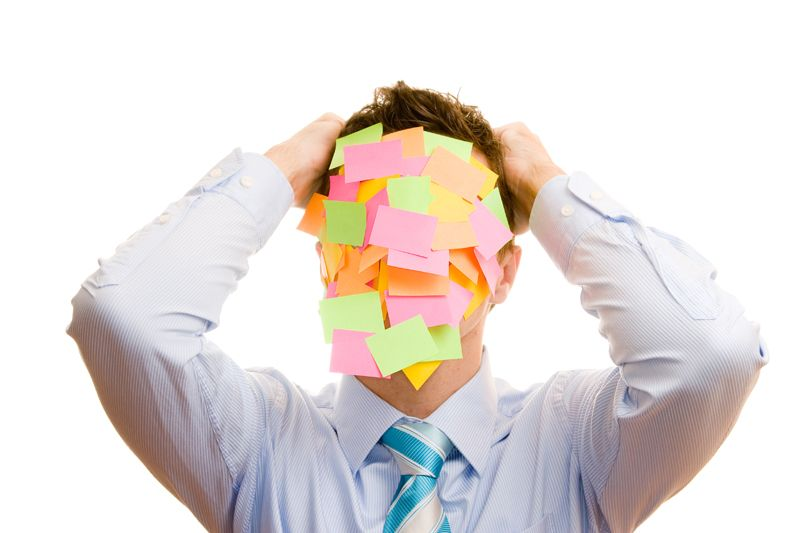 Businessman covered with memos on white background